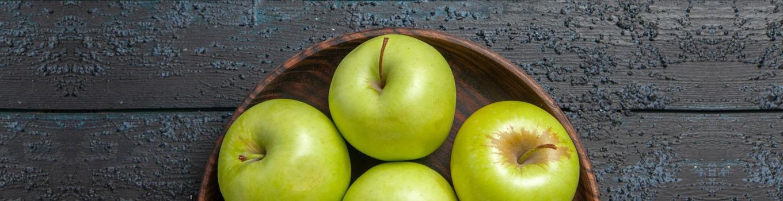 تعدادی سیب در ظرف چوبی روی میز