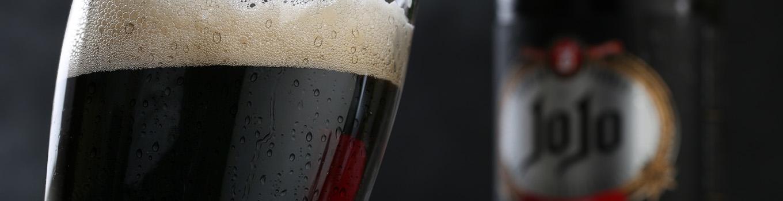 یک لیوان جوجو بلک در کنار بطری ماء الشعیر بلک جوجو