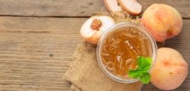 لیوان کوکتل هلو و هلو روی میز چوبی
