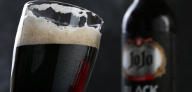 یک لیوان ماالشعیربلک جوجو در کنار یک بطری آبجو بلک
