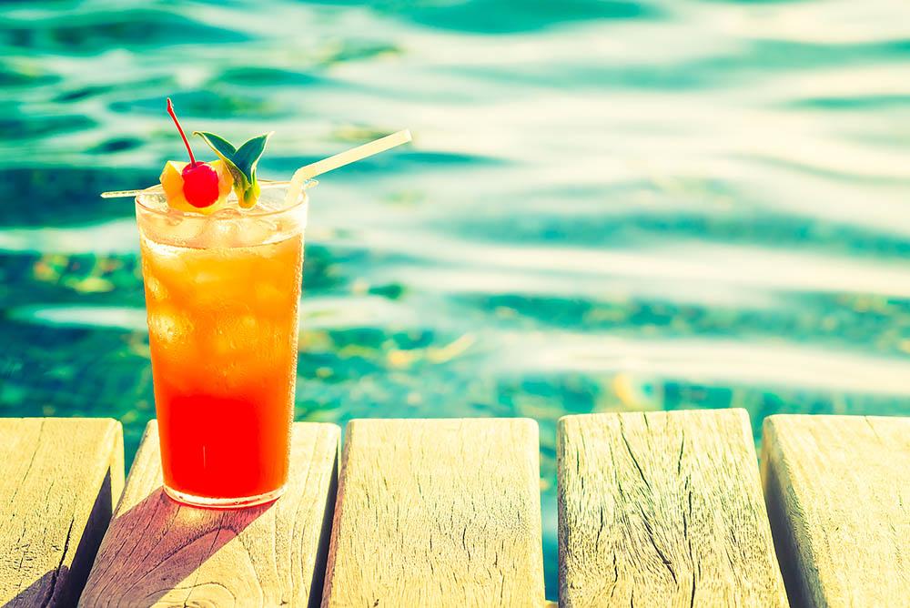 یک لیوان کوکتل هلو در کنار استخر