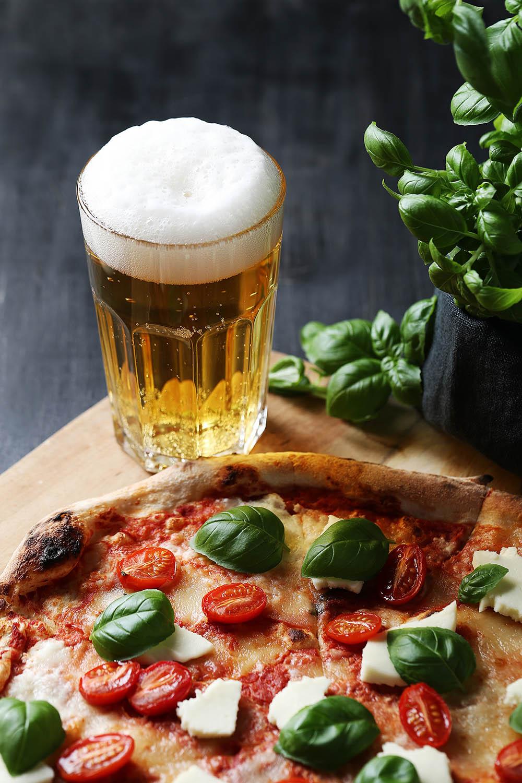 یک لیوان آبجو در کنار پیتزای گوجه و ریحان
