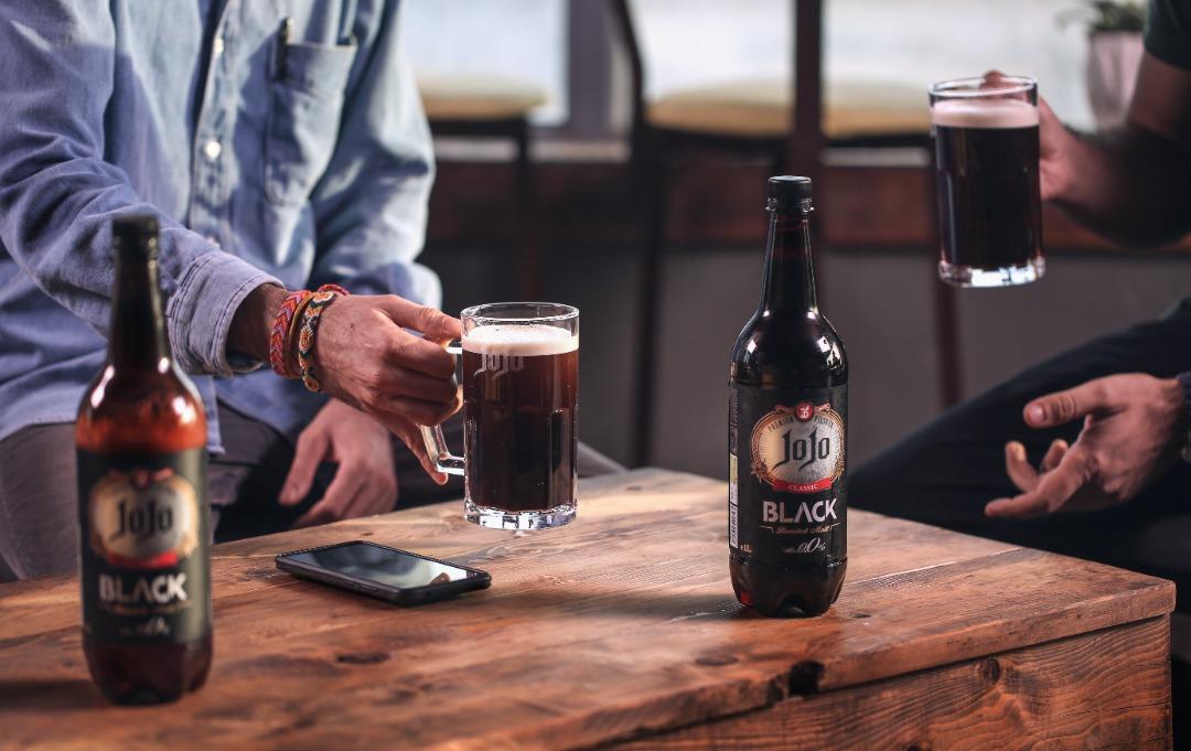 دو دوست در کنار هم در حال نوشیدن جوجو بلک و بطریهای بلک روی میز